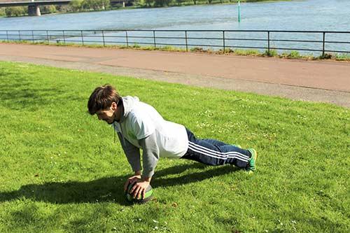 Medizinball Workout - Übung Liegestütz eng mit Mountain Climber